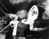 """Father Christmas riding in his sleigh, c 1940s."""