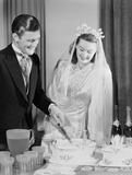 """Bride and groom cutting their wedding cake, c 1949."""
