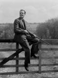 """Man with a shotgun sitting on a gate, 1951."""