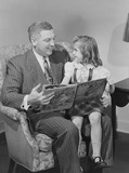 """Man reading a story to a child, 1949."""