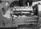 """Mechanic working on a Bugatti racing car, Nurburgring, Germany, 1932."""