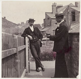 Man taking a photograph with a Brownie camera, c 1900