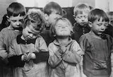 Infants' school children praying in silence during the school's religious assembly, 1937.