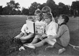 Five children sitting in the park reading a 'Bobby Bear's' annual, c 1930s.