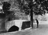 Man painting beneath a tree by a bridge c.1930s