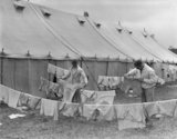 Two men hanging their laundry on a line connected to a tent.