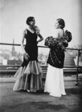 Two women modelling evening gowns on a roof-top.