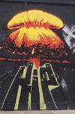 Graffiti of mushroom cloud over city scape in East London