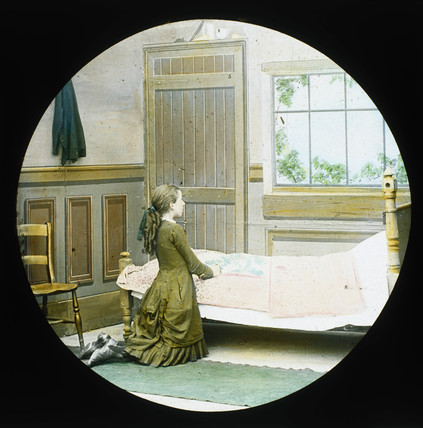 A girl kneeling in prayer at her bedside. M