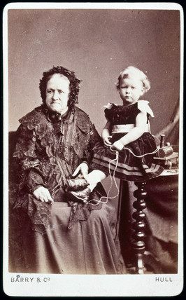 An elderly lady and a young child with a toy train, c 1870.