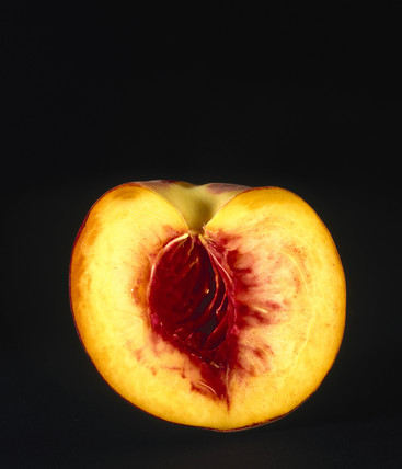 A peach, cut in half, with the stone removed, 1990s.