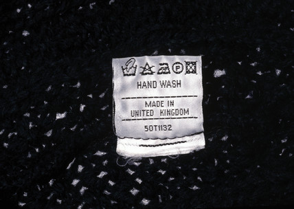 Clothing label showing washing instructions, c 1990s.