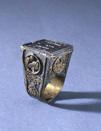 Finger ring with receptacle and hinged lid.