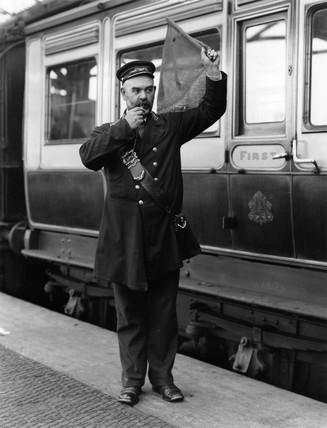 A guard waving his flag, Holyhead Station, c 1905.