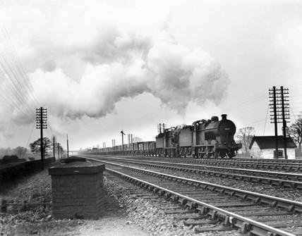 Two Clas 4F 0-6-0 steam locomotives head a coal train, c 1930s.