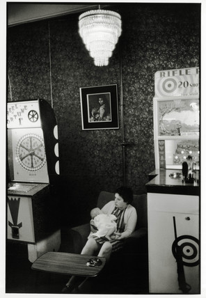 Young woman with a baby seated in amusement arcade, 1969.