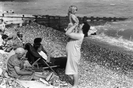 Woman holding child on shingle beach with other members of family, 1969.