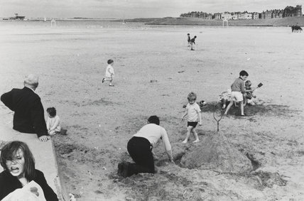 Group of children building sandcastles and playing cricket on the beach, 1967.