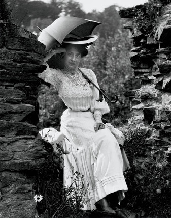 Edwardian woman sitting on a wall, c 1900s.