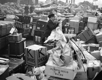 A station luggage handler surrounded luggage, 20 December 1936.