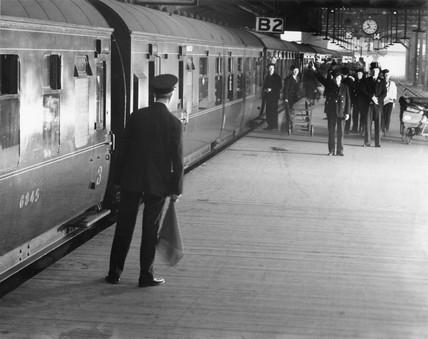 Station guard on platform, Euston station, London, 1938.