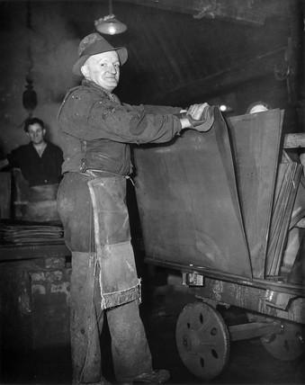 Dai Ward, a tinplate worker, holding a shee