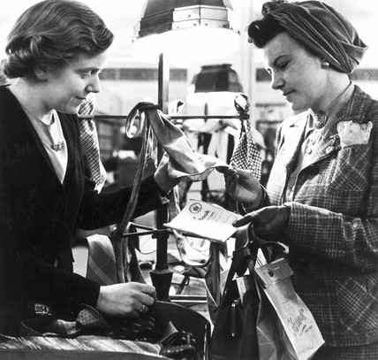 Shopping with clothing coupons, World War Two, c 1942.