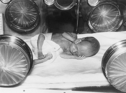 Baby lying in an incubator, January 1962.