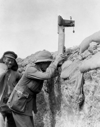 Soldier taking a photograph with a camera attached to a periscope, c 1915.