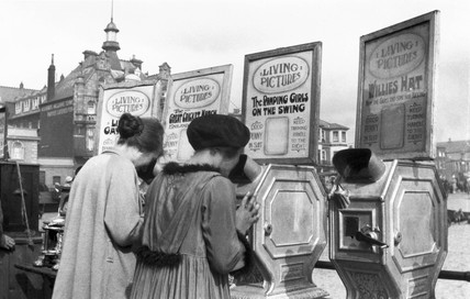 Two women peering into mutascopes, c 1930s.