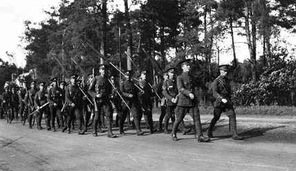 Soldiers marching with rolled-up flags, c W
