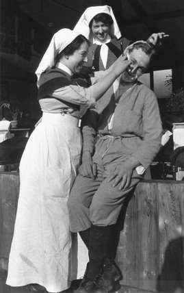 Nurse shaving a soldier with another nurse in close attendance, c 1910s.