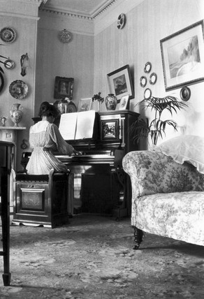 Woman playing the piano in an Edwardian dra