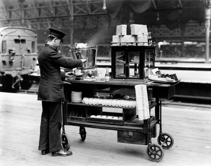 Attendant filliing teacup with boiling water from urn on trolley, 19 April 1921.