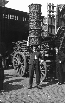 Market porter balancing baskets on his head, London, c 1910s.