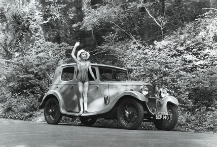 Girl in a swimming costume with a Riley car, c 1930s.