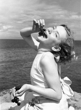 Girl eating cherries by the sea, c 1920s.