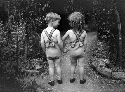Young boy and girl wearing identical swimming costumes, c 1930s.