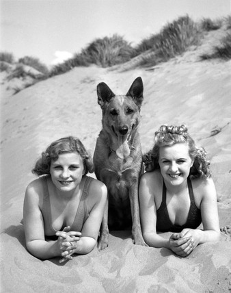 Dog flanked by two women, c 1930s.