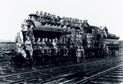 Women locomotive cleaners sitting on an engine.