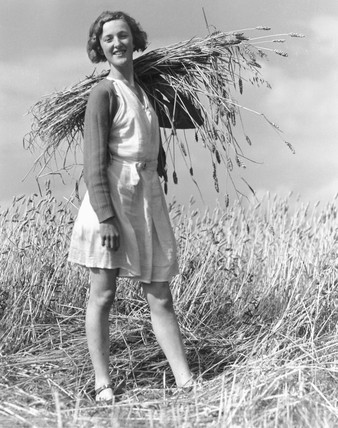 Land-girl with a sheaf of wheat over her shoulder, c 1930s.