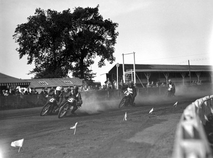 Speedway riders rounding a dirt-track corne