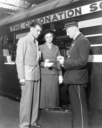 Conductor checking the booking of a young couple, 1937.