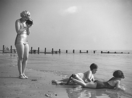 Woman in a bathing costume filming children