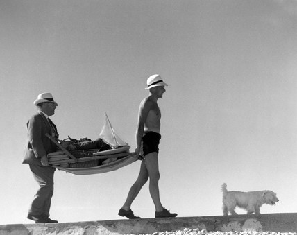 Two men carrying a deckchair laden with hol
