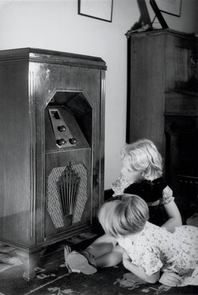 Two children listening to a GEC radio receiver, c 1930.