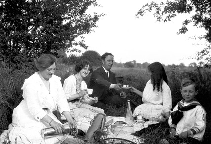 Family picnicking in the countryside, c 191