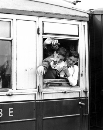 Schoolboys waving through the window of the train, June 1955.