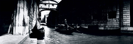 Panoramic view of a gondola on a canal in Venice, c 1910s
