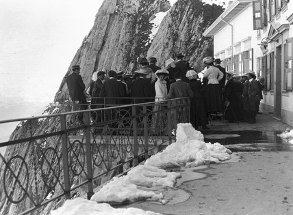 People gathered by a chalet on a mountain p